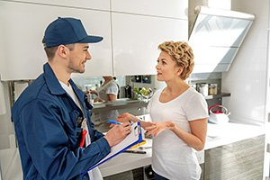 Interested housewife is talking to cheerful handyman with smile. Repairman holding folder. They are at kitchen