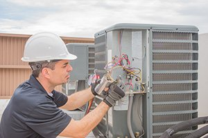 HVAC technician working on a capacitor part for condensing unit.