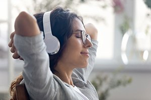 Catching inspiration. Close up of pretty young lady sitting on chair in modern multimedia device headphone set on head. Millennial woman rest with closed eyes listen to music audiobook study language