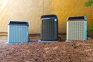 Multiple Air Conditioner Compressors next to large house or building, with room for copy space